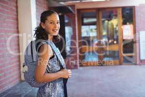 Happy schoolgirl standing with schoolbag in school campus