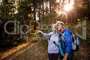 Hiking couple holding a compass and pointing