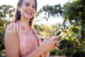 Portrait of smiling woman using her mobile phone in the park
