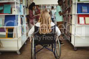Disabled girl on wheelchair in library