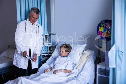 Doctor showing medical report in digital tablet to patient