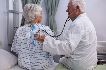 Doctor examining senior patient with stethoscope