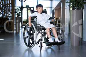 Disabled boy patient on wheelchair in hospital corridor