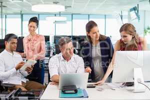 Business colleagues interacting with each other at desk in office
