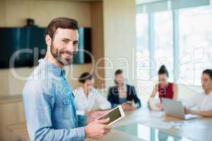 Portrait of smiling female business executive standing in conference room with digital tablet