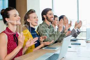 Business team applauding during meeting in conference room