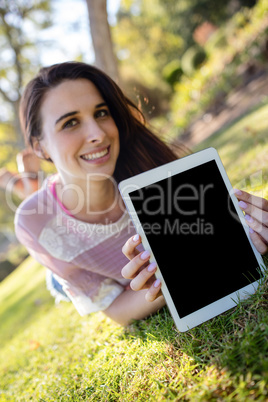 Woman lying on grass and holding digital tablet