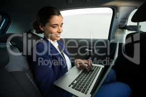 Business executive using laptop in car