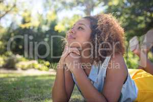 Thoughtful woman lying on a grass