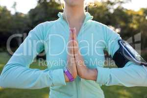 Mid section of female jogger listening to music and exercising with hands joint