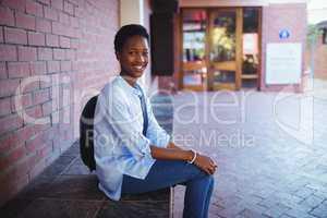 Happy schoolgirl sitting with school bag in school campus