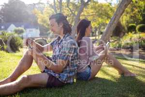 Young couple text messaging on mobile phone
