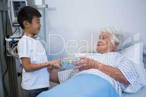 Boy giving a gift to senior patient on bed