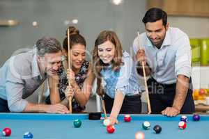 Smiling business colleagues playing pool