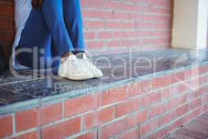 Schoolgirl sitting against brick wall
