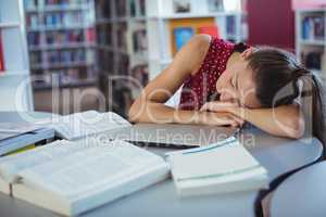 Tired schoolgirl sleeping while studying in library