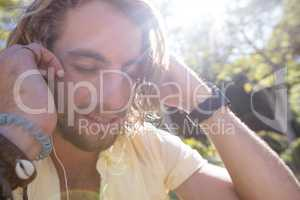 Close-up of man listening to music with earphone