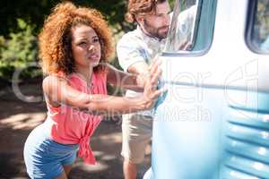 Couple pushing a campervan