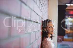 Happy schoolgirl sitting against brick wall in school campus
