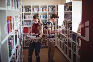 Attentive classmates reading book in library