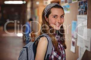 Portrait of smiling schoolgirl standing near notice board in corridor