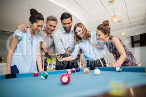 Business colleagues using mobile phone while playing pool in office space
