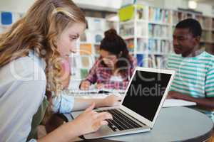 Attentive schoolgirl using laptop with her classmates in studying background