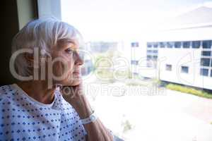 Thoughtful senior patient looking through window