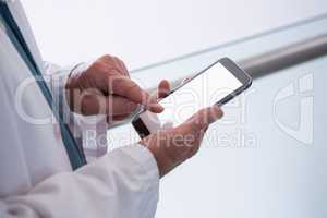 Doctor holding smartphone in the passageway at hospital