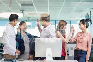 Business colleagues giving high five during meeting at desk in office