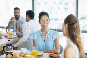 Business colleagues having breakfast together in office cafeteria
