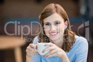 Smiling businesswoman drinking cup of coffee in office cafeteria