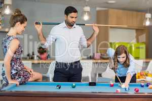 Business colleagues playing pool in office space