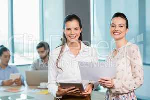 Female business executives standing with document and digital tablet in conference room