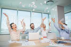 Happy business executives throwing crumpled paper in air