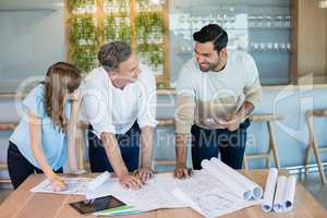 Architects discussing with each other in conference room