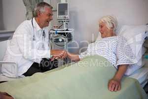 Doctor examining senior patient in ward