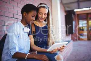 Schoolgirls sitting against brick wall and using digital tablet