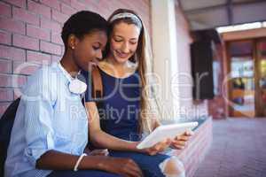 Schoolgirls sitting against brick wall and using digital tablet
