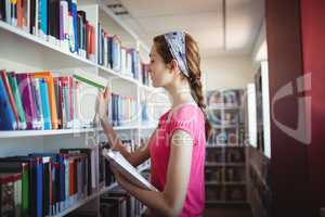 Schoolgirl selecting book from book shelf in library