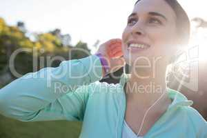 Close-up of smiling female jogger with headphones taking a break from exercise