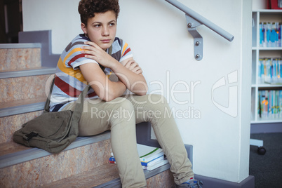 Sad schoolboy sitting alone on staircase