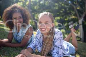 Female friends lying together on grass in park