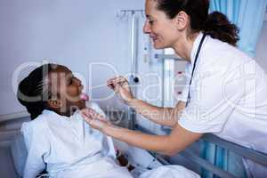 Doctor checking patient fever from thermometer during visit in ward