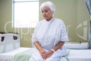 Worried senior patient sitting on bed