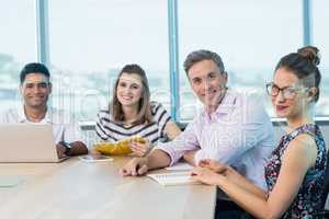Portrait of smiling business colleagues with laptop in meeting