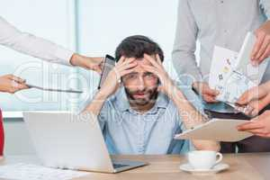Colleagues with document, digital tablet and mobile phone talking to frustrated man