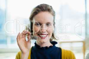 Smiling female business executive with headset sitting in office