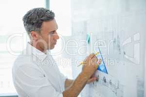 Architect drawing on blueprint at whiteboard