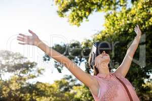 Woman raising her hands while using a VR headset in the park